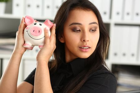 young beautiful brunette woman hold piggybank in arms Stockfoto