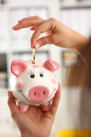 woman hand put coin into funny smile piggybank collect money concept