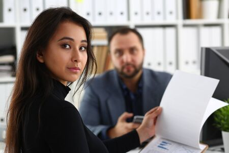 young beautiful woman sit on chair at table in office in cabinet of her boss hold binder in arms work with documents Stockfoto