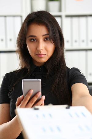 portrait of young beautiful brunette businesswoman work in office like her job hold smartphone and binder in arms