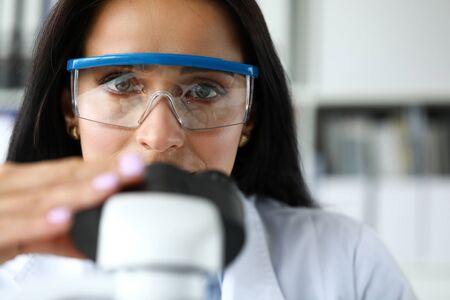 Beautiful mature assistance using scientific microscope portrait