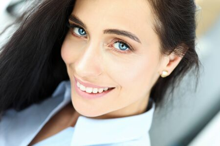 Portrait of beautiful cheerful woman sitting at workplace