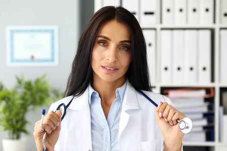 Pretty adult caucasian female GP stretching stethoscope in hands with pride facial expression looking in camera headshot