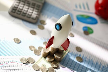 White space rocket make business startup against money and chart background. Financial education concept