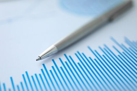 Silver pen lies on paper documents with color business charts background. Statistics financial analysis concept. Development of stock markets and securities strategies
