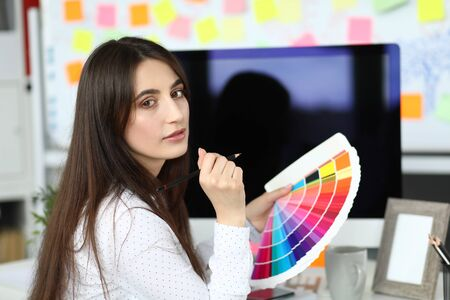 Portrait of beautiful creator choosing color scheme. Wonderful designer looking at camera with calmness. Business and art design concept. Blurred background Reklamní fotografie