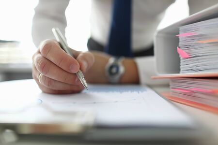 Male businessman hold silver pen in hand against business chart background. Office work. Business education concept.