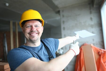 Portrait of happy man wearing gloves and hardhat showing something with paper tablet. Thoughtful male posing in big unfinished room and smiling. Building concept