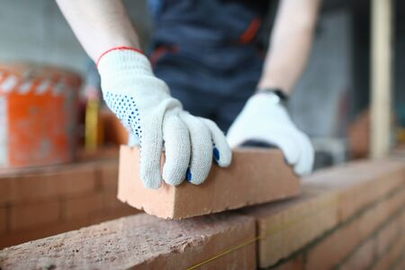 Close-up of male hands putting red blocks on concrete wall in order to achieve task in constructing new structure. Prudent constructor wearing protective gloves. Building concept