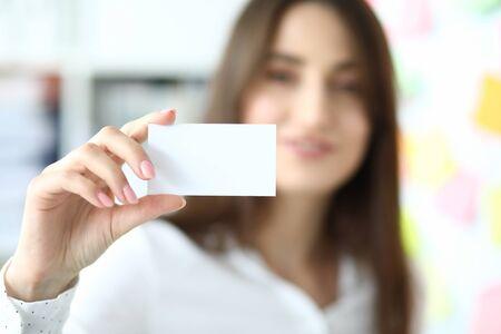 Concentrez-vous sur la main tendre d'une femme d'affaires souriante montrant une carte de visite vierge spéciale à un collègue ou à un partenaire amical. Copiez l'espace sur la table de montage biz. Arrière-plan flou