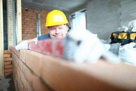 Portrait of cheerful and concentrated builder wearing hard hat and construction gloves to prevent any harm. Smart male using special equipment to measure level of brick wall. Building concept