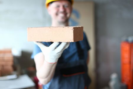 Focus on male hand presenting concrete block. Happy smiling constructor man in protective outfit holding red brick in one hand and looking at camera with gladness. Building concept Фото со стока - 129199479