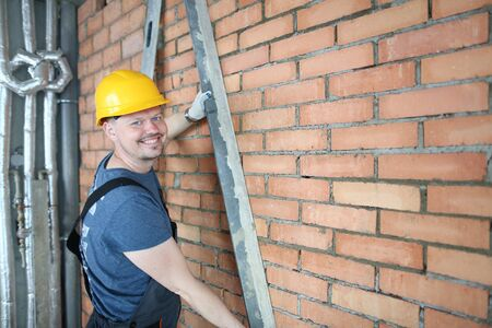 Portrait of man using special construction equipment to remove any concrete masses to make wall made of red brick smooth and easy to plaster surface. Male posing in unfinished room. Building concept Stock Photo