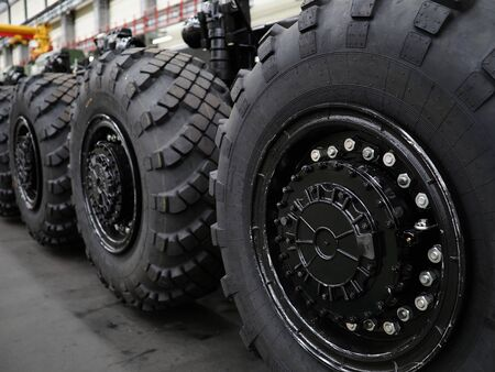 Heavy wheeled tires tractor on assembly line of the plant for transport non-standard cargo unusual background