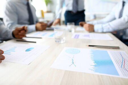 El gráfico de negocios se encuentra en la mesa contra el fondo de la oficina de personas del grupo. Seminario concepto de análisis de estadística financiera. Lección de educación en el aula Foto de archivo