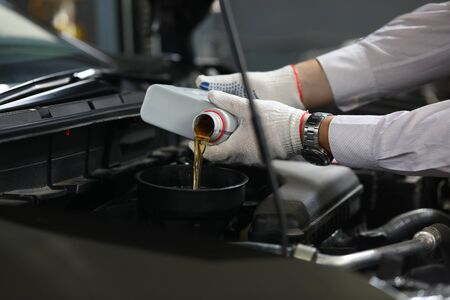 Male hand in white protective gloves with funnel change mineral motor oil in car engine. Liquid professional petroleum concept 写真素材