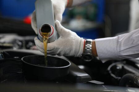 Male hand in white protective gloves with funnel change mineral motor oil in car engine. Liquid professional petroleum concept Stockfoto