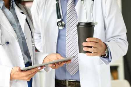 Two GP using mobile application on tablet pc closeup