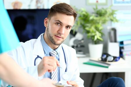 Portrait of intelligent man wearing white robe and stethoscope. Handsome doctor writing something in tablet and looking at camera with calmness. Medical treatment concept