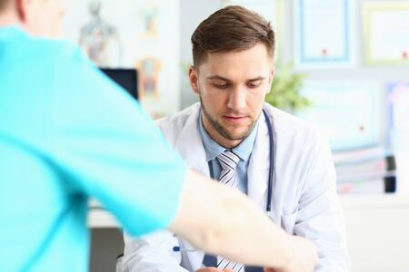 Portrait of sullen doctor having disturbing conversation with colleague. Bearded boy looking down. Man wearing classy blue shirt white robe and striped tie
