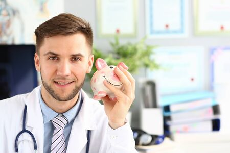 Portrait of cheerful doctor shaking piggy bank. Happy physician posing in polyclinic cabinet in white uniform with stethoscope and looking at camera with certainty. Health insurance policy concept Фото со стока - 129200341