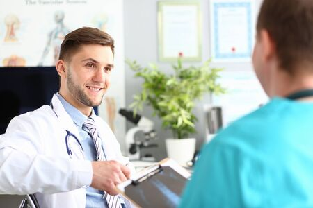 Portrait of smart physician looking at friend with trustful smile. Medical men sitting in big clinic office and discussing treatment. Medicine and healthcare concept