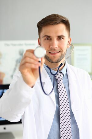 Portrait of smiling man with medical instrument. Cheerful doctor trying to listen action of heart or breathing. Physician looking at camera with gladness. Medicine and health care concept Фото со стока - 129200367