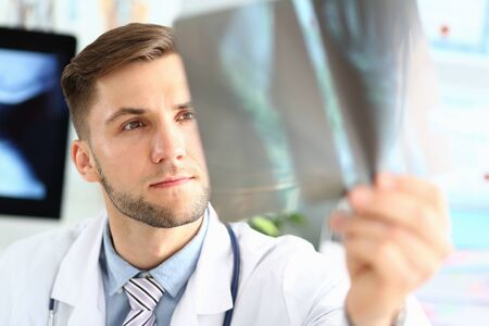 Portrait of thoughtful doc examining x-ray picture. Concentrated physician making diagnosis. Medical treatment and health care concept. Blurred background