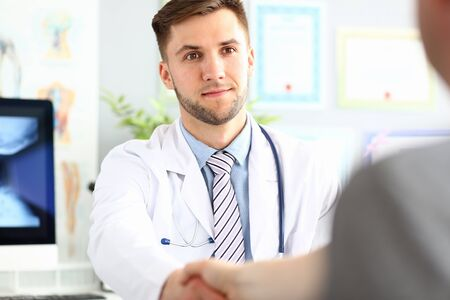 Portrait of smiling doc saying hello or goodbye to patient. Physician wearing white uniform and stethoscope. Man looking at visitor with gladness. Blurred background