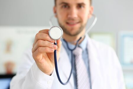 Focus on male hand holding stethoscope. Smiling doctor listening to action of heart or breathing. Medicine and health care concept. Blurred background