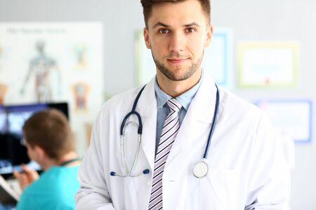 Portrait of attractive physician standing in polyclinic wearing white hospital robe and stethoscope. Bearded guy looking at camera with calmness and interest. Medical treatment concept