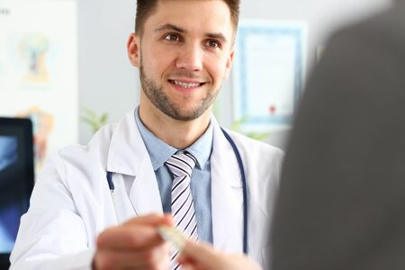 Portrait of smiling doctor giving sick man pills and recommendation using of drugs. Doc wearing medical robe and stethoscope. Medical concept. Blurred background