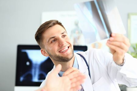 Portrait of smiling doctor delighting good x-ray picture results. Physician looking at sciagram with gladness. Medical treatment and healthcare concept. Blurred background