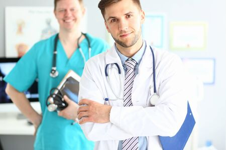 Portrait of handsome man in white coat with stethoscope. Smiling doctor standing with arms crossed in clinic office. Medical treatment concept. Blurred background