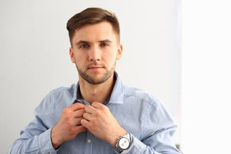 Portrait of confident male looking at camera with interest and confidence. Smart man wearing blue shirt and expensive watches in modern studio. Isolated on white Фото со стока