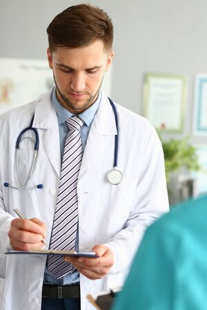 Portrait of physician looking down at notepad overwhelmed with concerns. Man wearing white robe, stethoscope and trendy striped tie. Smart boy posing in clinic. Medical treatment concept