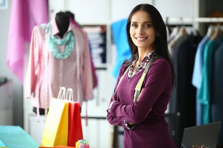 Portrait of joyful woman standing in modern workplace and looking at camera with calmness and tenderness. Successful businesswoman posing in fashionable outfit. Fashioner workshop concept