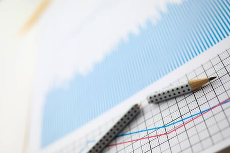 Broken pencil lies on table against background of business charts. Improper business concept Stock fotó