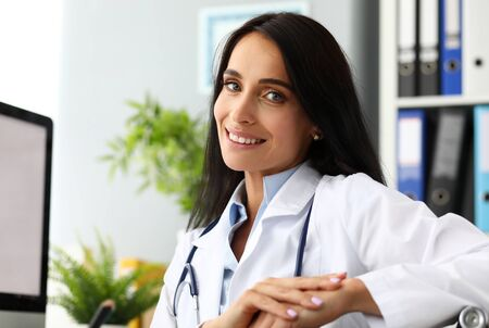 Mature female GP sitting at working table arms crossed looking in camera portrait