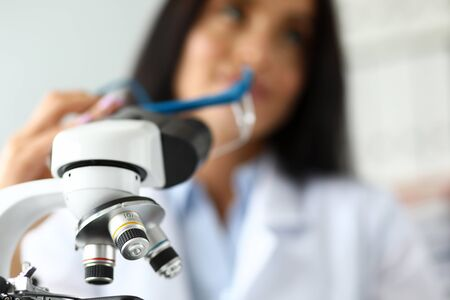 Scientific microscope lens with female analyst in background close-up