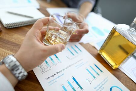 Two business people hold glass with whisky against chart background. 10 october boss day concept.
