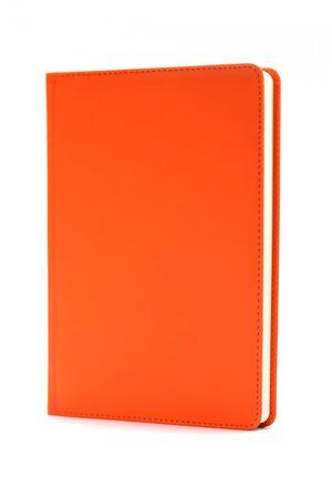 Orangefarbenes Tagebuch isoliert auf weißem Hintergrund. Konzept der kaufmännischen Bildung. Bürobedarf. Standard-Bild