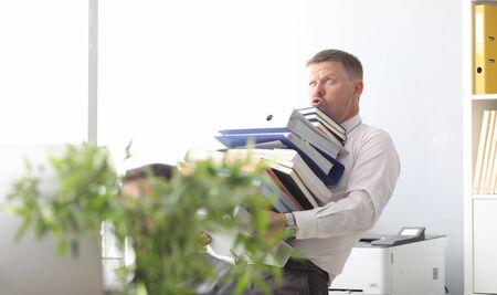 Männlicher Geschäftsmann trägt eine Reihe von Ordnern und Dokumenten in der Hand vor Bürohintergrund. Viel Arbeit Loser-Konzept.
