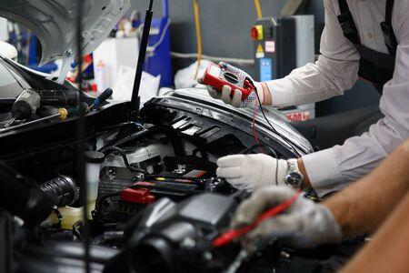 Dos especialistas del servicio de reparación de cableado y diagnóstico informático del coche solucionan el problema del mal funcionamiento del motor. Serviceman colabora el concepto de formación educativa. Estudio de nuevas tecnologías