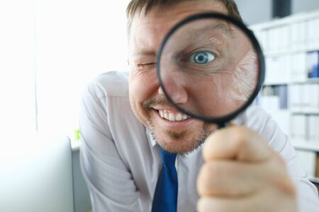 Smiling businessman hold magnifying glass in hand. Where to invest profit search concept