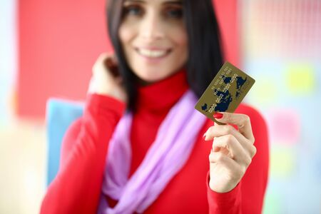 Focus on tender female hand with red manicure holding special banking utility. Joyful woman wearing trendy and fashionable outfit. Happy shopping concept. Blurred background Reklamní fotografie