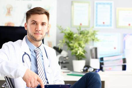 Portrait of handsome man looking in camera with joy and sitting in chair. Trendy man wearing white laboratory coat and stethoscope. Medical and healthcare treatment concept Stock Photo