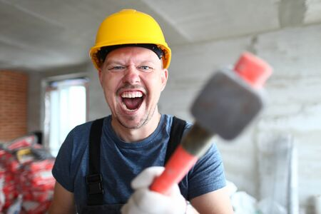 Portrait of screaming male holding big sturdy construction tool. Scary builder laughing at camera with joy and madness. Strange guy wearing yellow hardhat and bricklayer outfit. Building concept