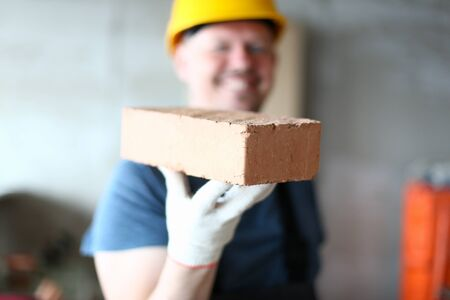 Focus on serious brick in male hand. Worker in hardhat presenting red block to camera with big smile. Joyful constructor in yellow helmet looking with happiness on face. Building concept