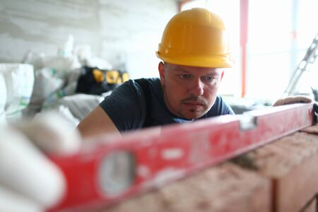Portrait of smart male using special equipment to remain certain quality of construction method level. Bearded builder wearing hard gloves to keep hands unharmed. Building concept Stok Fotoğraf